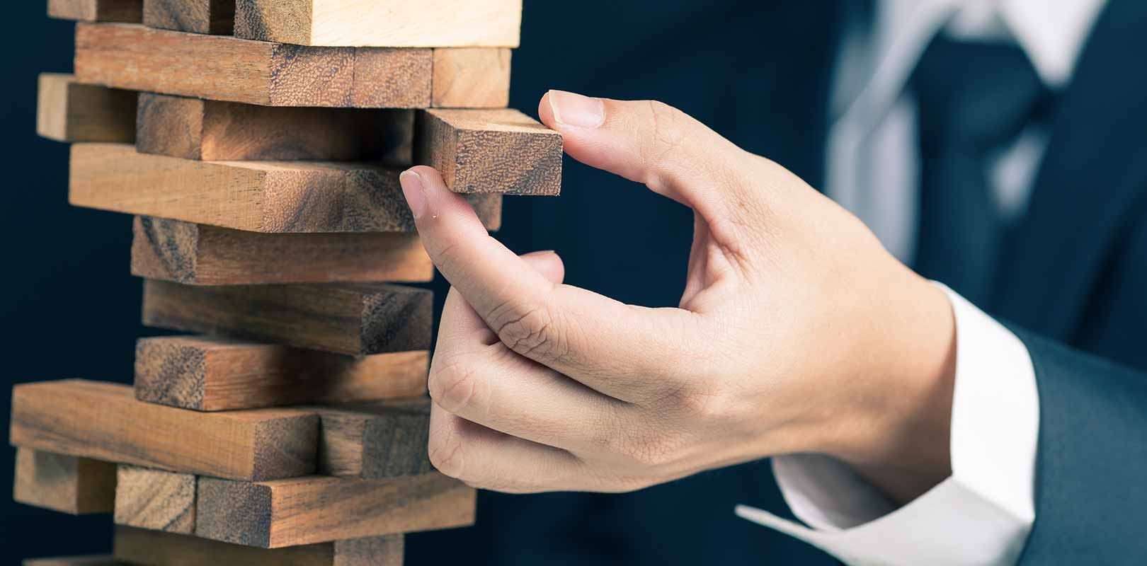 A businessman with Jenga blocks to signify risk