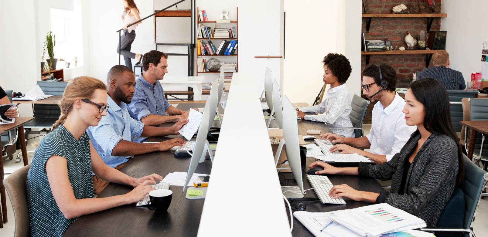 Employees working in an office at a long shared desk